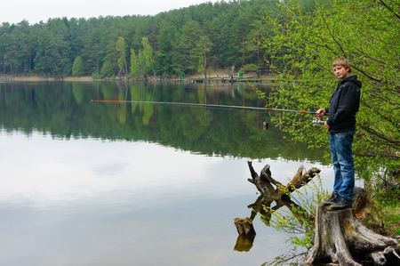 children pond: Boy fishing on the shores of beautiful Lake