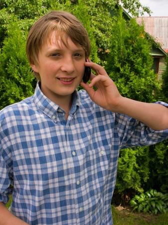 Teenager boy talking on a cell phone photo