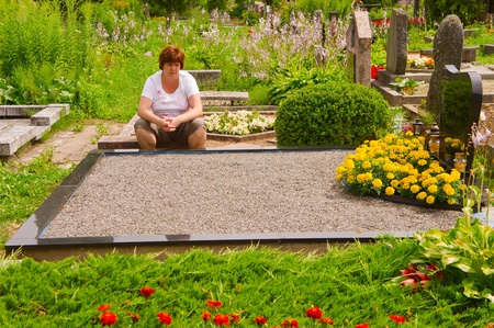 Woman  praying next to grave in cemetery
