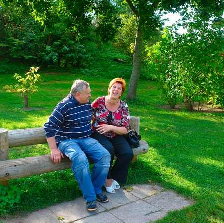Happy elderly couple talking in the park Stock Photo