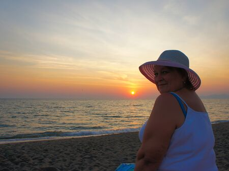 Mature woman in a hat relaxing near the sea on sunset   photo