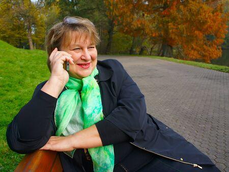 An elderly woman in  autumn park  talking on the phone Stock Photo - 11227496