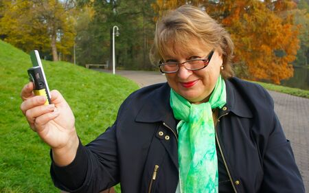 Portrait of middle-aged women in  autumn park  talking on the phone Stock Photo - 11536604