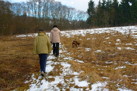 Mother and son walking in a winter forest photo