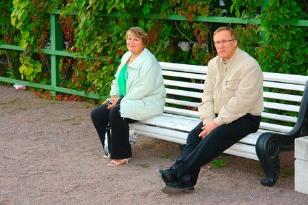 Older couple sitting on a bench at the park photo