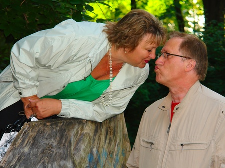 Senior couple on a picnic, kissing in the park. photo