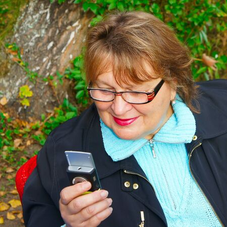 Mature woman  dialing a number on her cell phone. photo