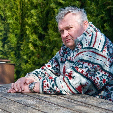 Portrait of an elderly man sitting at a wooden table in the park photo