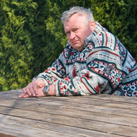 Portrait of an elderly man sitting at a wooden table in the park Stock Photo - 13417133