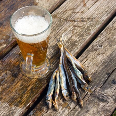 near beer: Dried fish fish near the glass of beer