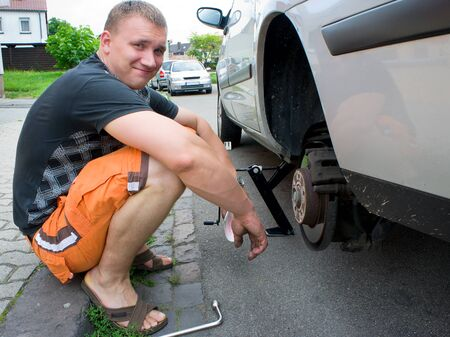 Man changing the car wheel on the road Stock Photo - 13894659