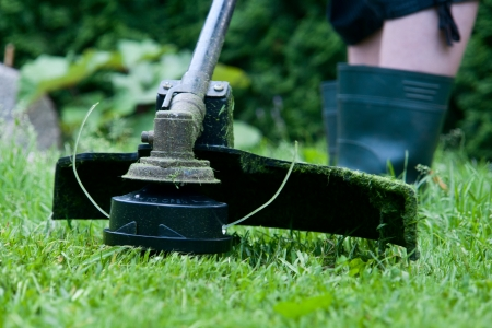 Electric lawn trimmer on an oblique grass.
