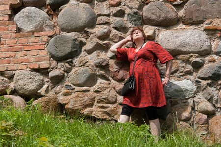 Portrait beautiful happy middle aged woman standing  relaxed on sunny day outdoor wall Stock Photo - 17370410