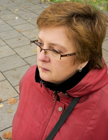 Portrait of a middle-aged woman in a red jacket and glasses photo