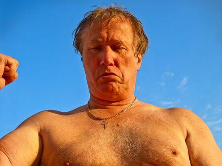 Senior man grimacing. Angry caucasian man. Close-up portrait on blue background.