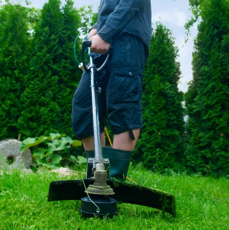 Guy with lawn mower in front of back yard Stock Photo
