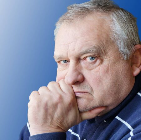 Portrait of the elderly man on a blue background. Stock Photo - 18602302