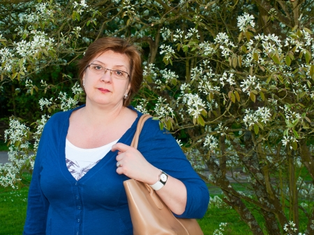 Middle-aged woman in the park in a blue sweater Stock Photo