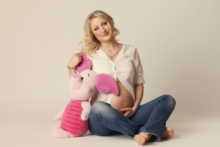 A pregnant woman with a plush toy in the hands of Stock Photo