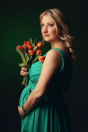 Happy young pregnant woman with tulip flowers in their hands photo