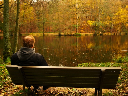 A middle aged man resting on a bench by the lake photo