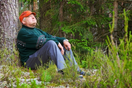 Old man resting in a forest near a tree photo