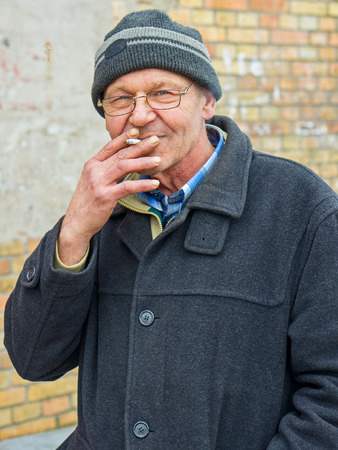 grey haired: Elderly grey haired  man wearing glasses and a knitted cap enjoying a cigarette outdoors in winter woodland exhaling smoke and looking intently into the camera