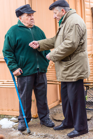 sidewalk talk: Two serious senior men talking in courtyard