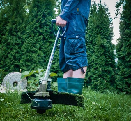 clippers: Guy with lawn mower in front of back yard Stock Photo
