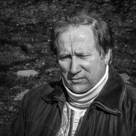 Black and white close up portrait of a mature man in deep thought. photo