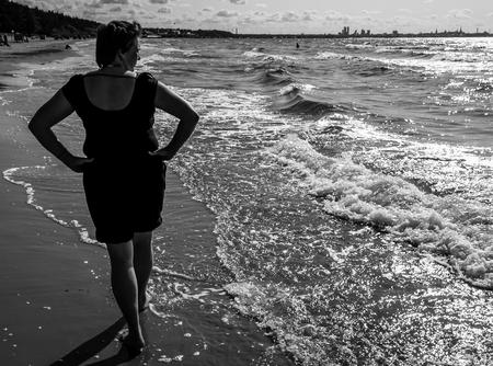 Mature blonde enjoying the sea. Black & white photo