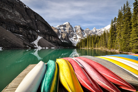 Coloured canoes lined up at edge of Moraine Lake, Banff National Park, Canada