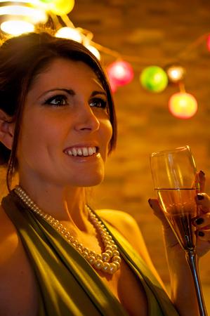 cocktaildress: Vrouw bij partij dragen groene cocktail jurk, parelsnoer en drinkiing champagne - kerstverlichting in de achtergrond. Stockfoto