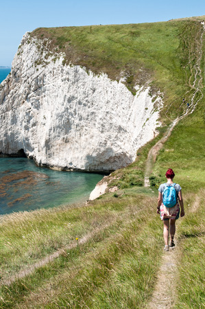 durdle door: A young female hiker walks The South West Coastal Path, Dorset. Durdle Door in distance. Part of The Jurassic Coastline of England.