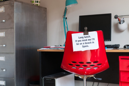 Employee leaves note pinned to chair to tell colleagues that  if they are needed, they can be found on a beach in Spain! photo