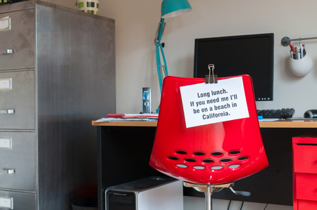 Employee leaves note pinned to chair to tell colleagues that  if they are needed, they can be found on a beach in California! photo