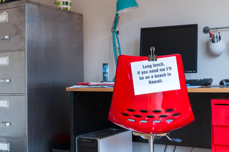 absence: Employee leaves note pinned to chair to tell colleagues that  if they are needed, they can be found on a beach in Hawaii! Stock Photo