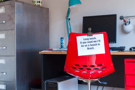 Employee leaves note pinned to chair to tell colleagues that  if they are needed, they can be found on a beach in Brazil! photo