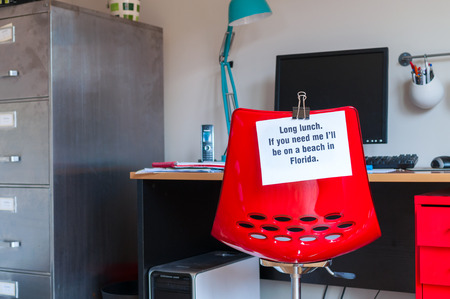 Employee leaves note pinned to chair to tell colleagues that  if they are needed, they can be found on a beach in Florida!