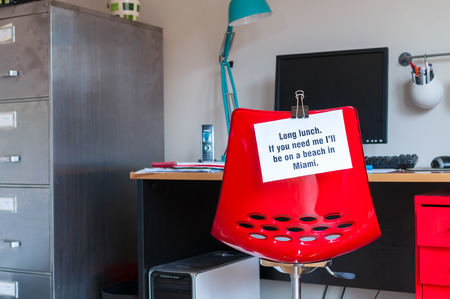 Employee leaves note pinned to chair to tell colleagues that  if they are needed, they can be found on a beach in Miami! photo