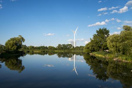 cielos azules: Proporcionando Windmill Energ�a Limpia Rodeado de cielos azules, de agua limpia, la hierba verde y los �rboles