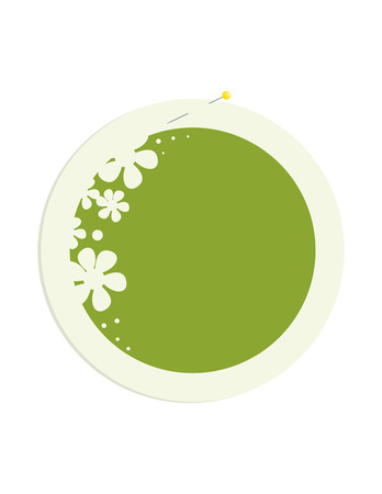 Round frame with a green center and flower decoration secured with a pin to a white background