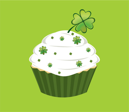 Cupcake decorated with green diamond shapes and shamrocks on white frosted in front of a white background