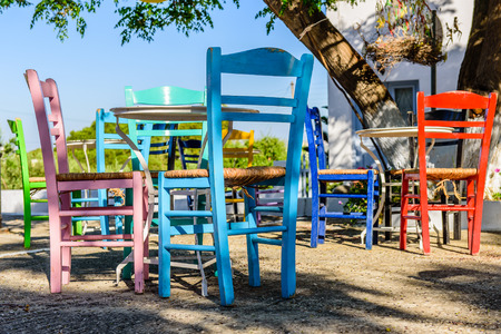 cycladic: Bright colorful chairs - a traditional cafe in Cycladic village of Plaka, Milos, Cyclades, Greece. Stock Photo