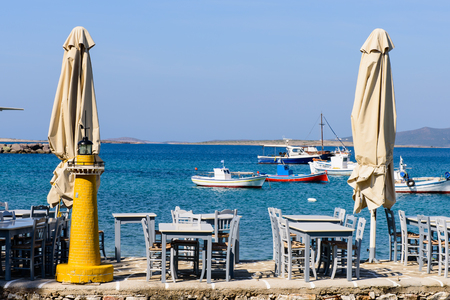 taverna: Paros island, Greece - JUNE 1:Traditional Greek taverna on the seafront on the beach - bright chairs and table in JUNE 1, 2015, Alyki village, Paros island, Cyclades, Greece. Editorial