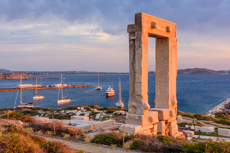 """Naxos island, Greece - JUNE 3: the Ancient marble gate """"Portara"""" - the entrance to the temple of Apollo in JUNE 3, 2015, Naxos island, Cyclades, Greece."""