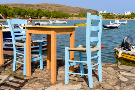 taverna: Milos island, Greece - MAY 27: Traditional Greek taverna on the seafront on the beach - bright chairs and table in MAY 27, 2015, Milos island, Cyclades, Greece.