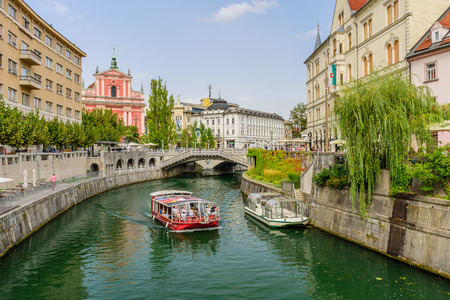 Ljubljana, Slovenia - September 10, 2016: the scenic Ljubljanica river with weeping willows on the embankment. Editorial