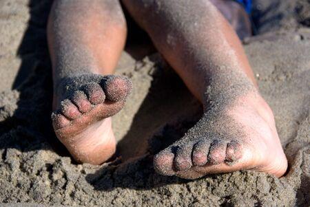 pieds sales: Childs accroch� les pieds avec du sable sur les jambes et les pieds Banque d'images