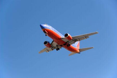 Passenger Jet coming in for a landing against blue sky.